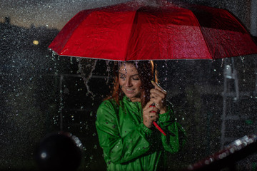 Young woman in green raincoat in rain with red umbrella at night. Smiling young woman in the rain with an umbrella in the evening. Beautiful woman with red umbrella in lanterns and rain drops