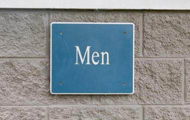 A men restroom sign on the brick wall and a close view.