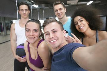 Group of sportive people taking selfie in gym
