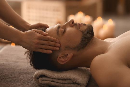 Young man receiving massage at spa salon