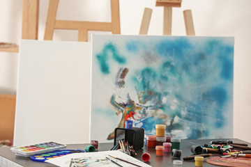 Paints and tools of professional artist on table