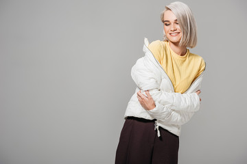 happy young woman in stylish white jacket posing isolated on grey background Wall mural