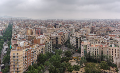 View to Barcelona city from the top of the basilica in a dull, murky day with a very grey and overcast sky. Barcelona skyline under heavy grey clouds.
