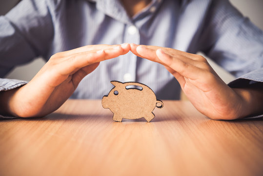 Hand protecting the icon piggy bank - the concept of insurance for Deposit