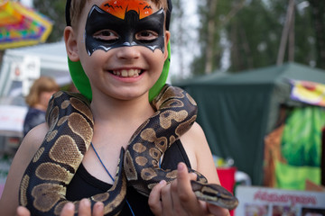 Child with the picture on the face of batman holding in the hands of the snake on ethno festival