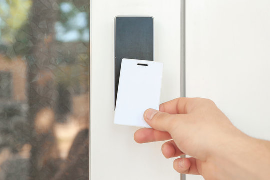 Man opening door with security card outdoors