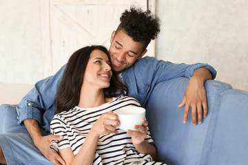Happy African-American couple drinking tea at home