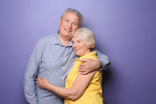 Happy senior couple on color background