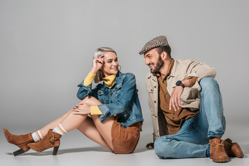 stylish couple sitting in autumn outfit and looking at each other, on grey Wall mural