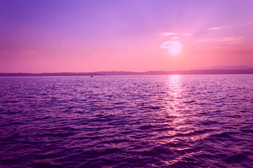 Beautiful purple sunset with floating boat on Lago di Garda near Scaliger Castle, Sirmione, Italy, romantic love concept