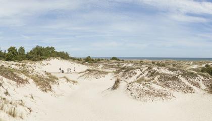 Dünen am Meer, Menschen laufen über Steg, Ostsee