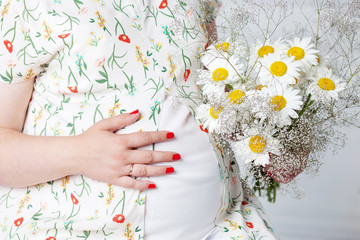 Closeup of pregnant woman holding flower and touching her belly