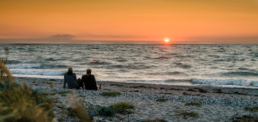 panorama of a couple in love sitting on the beach and looking at the sunset.