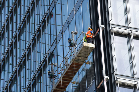 Construction workers on a suspended platform on a skyscraper