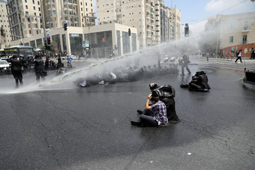 Ultra-Orthodox Jewish men are sprayed with a water cannon by Israeli police as they block a road during a protest against the detention of one of their community members who evaded a military draft order, in Jerusalem