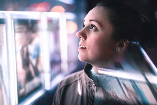 Serious thoughtful woman looking at city lights at night in dark. Dramatic face with reflection of billboard signs. Pensive lady thinking. Side view.