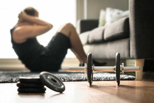 Home workout. Man doing ab training and crunches in living room gym. Guy doing sit ups. Warm up before weight exercise. Fitness concept with dumbbell and athlete.