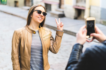 Young smiling woman posing for camera phone and showing victory sign with hand. Man taking photo with smartphone of friend or girlfriend. Tourist in city street. Travel, tourism and mobile photography