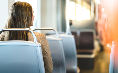 Back view of young woman sitting in public transportation. Passenger riding the bus, train, tram or subway. Happy female traveler. Commute or vacation. Lady going to work.