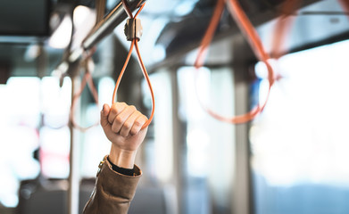 Hand holding the handle in tram, train, bus or subway. Passenger standing in public transportation. Person commuting. Commuter going to work.
