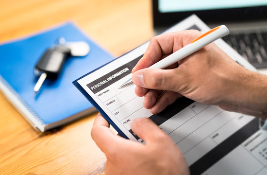 Car insurance form, bank loan, lease agreement or repair contract. Man writing personal information to document. Customer buying or salesman selling vehicle. Dealer or rental. Keys on table.