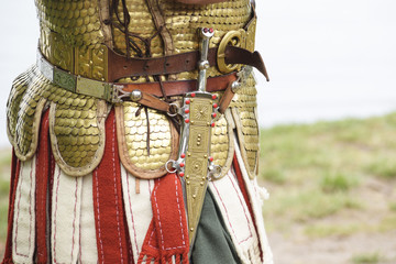 detail of an ancient roman soldier, legionnaire or centurion wearing a Lorica Squamata armor and a dagger at a historical festival, copy space
