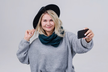 Happy cute woman making selfie over gray background. Wearing in bright scarf , sweater and hat. Looking at camera