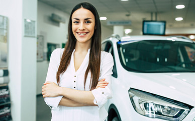 Smiling young beautiful woman in dealership. Beautiful woman buying a new car for job and travel in dealership, girl customer