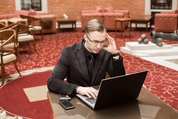 young successful businessman with laptop and phone