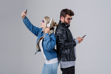 Portrait of a young couple enjoying music and make selfie over grey background