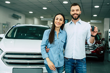 Happy young hugging couple chooses and buying a new car for the family in the dealership.