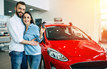 Happy young couple chooses and buying a new car for the family.
