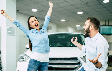 The successful visit to the dealership. Happy young couple chooses and buying a new car for the family.
