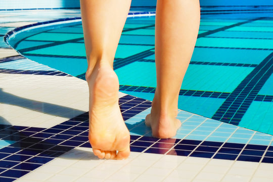 Close up of barefoot young woman with clean feet standing on edge of pool. Smooth female legs by outdoor poolside, spa hotel resort. Foot fungus & cracked heels medicine concept. Background copy space