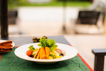 Vegetarian entrée for lunch meal with fresh carrot, salad, grape, olive, watermelon, served in a dish of a terrace.