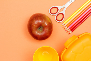 Apple, scissors, felt pens, color pencils and lunch box. School