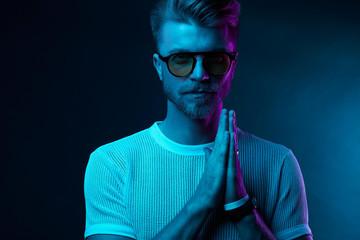 Neon light studio portrait of attractive male model in sunglasses and white t-shirt