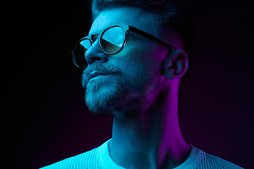 Neon light studio close-up portrait of serious man model with mustaches and beard in sunglasses and white t-shirt Wall mural