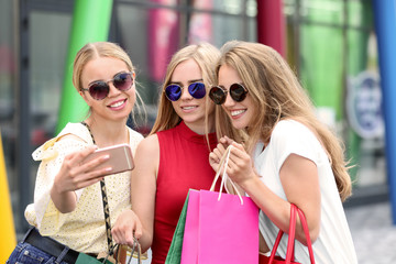 Young women with shopping bags taking selfie on city street