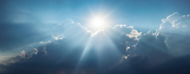 Panoramic view of clouds and sun with beautiful rays against the sky. Wall mural