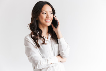 Photo closeup of beautiful chinese woman with long dark hair holding smartphone and having mobile call, isolated over white background in studio