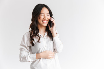Image of brunette chinese woman with long dark hair holding and talking on cell phone, isolated over white background in studio