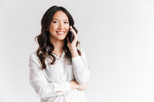 Image closeup of attractive chinese woman with long dark hair holding smartphone and having mobile call, isolated over white background in studio