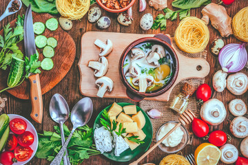 cooking meals mushrooms in batter with egg, herbs and milk. different food ingredients on a wooden background.