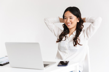 Photo of joyous chinese businesswoman with long dark hair sitting in office and working with documents and laptop, isolated over white background