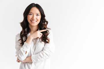 Joyful asian woman with long dark hair looking at camera with beautiful smile and pointing finger aside at copyspace text or product, isolated over white background in studio
