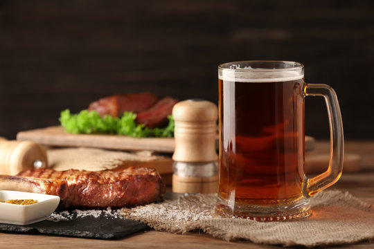 Mug of delicious beer with grilled steak on wooden table
