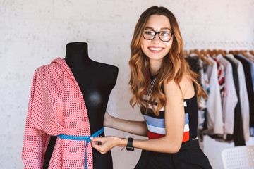 Positive young woman clothes designer at the atelier