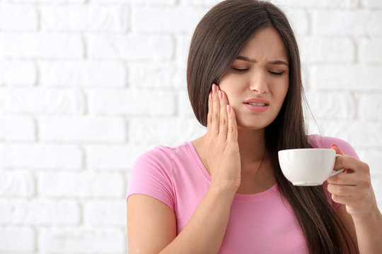 Young woman with sensitive teeth and cup of hot coffee on blurred  background
