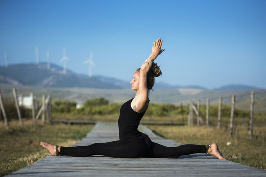 Woman on Los Lances beach doing front splits yoga pose, The Strait Natural Park, Tarifa, Cadiz, Andalusia, Spain